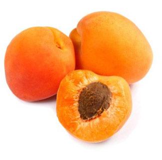 Un demi-abricot laissant apparaitre son noyau est posé au premier plan, devant 2 abricots entiers